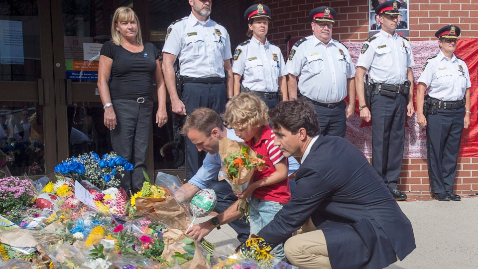 Prime Minister Justin Trudeau, accompanied by his four-year-old son Hadrien and Fredericton MP Matt DeCourcey, left, places flowers outside the police station in Fredericton on Sunday, Aug. 12, 2018. Two city police officers were among four people who died in a shooting in a residential area on the city's north side. THE CANADIAN PRESS/Andrew Vaughan