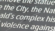 """Someone scratched a large """"X"""" across the temporary plaque outside Victoria City Hall Sunday. (CTV)"""