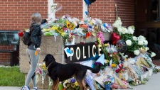 Flowers are placed on a makeshift memorial outside the police station in Fredericton on Saturday, Aug. 11, 2018. THE CANADIAN PRESS/Andrew Vaughan