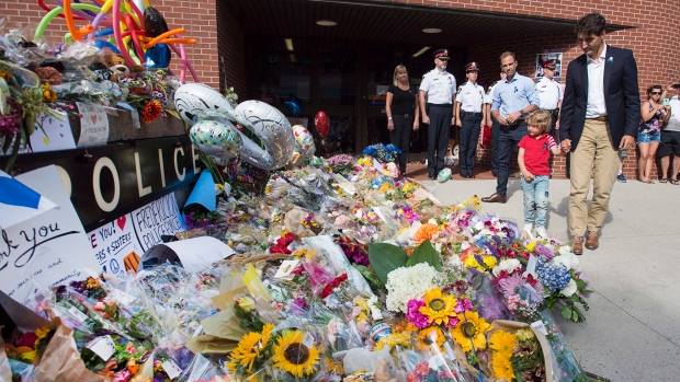 Prime Minister Justin Trudeau, accompanied by his four-year-old son Hadrien and Fredericton MP Matt DeCourcey, left, heads past the tribute after placing flowers outside the police station in Fredericton on Sunday, Aug. 12, 2018. (THE CANADIAN PRESS/Andrew Vaughan)