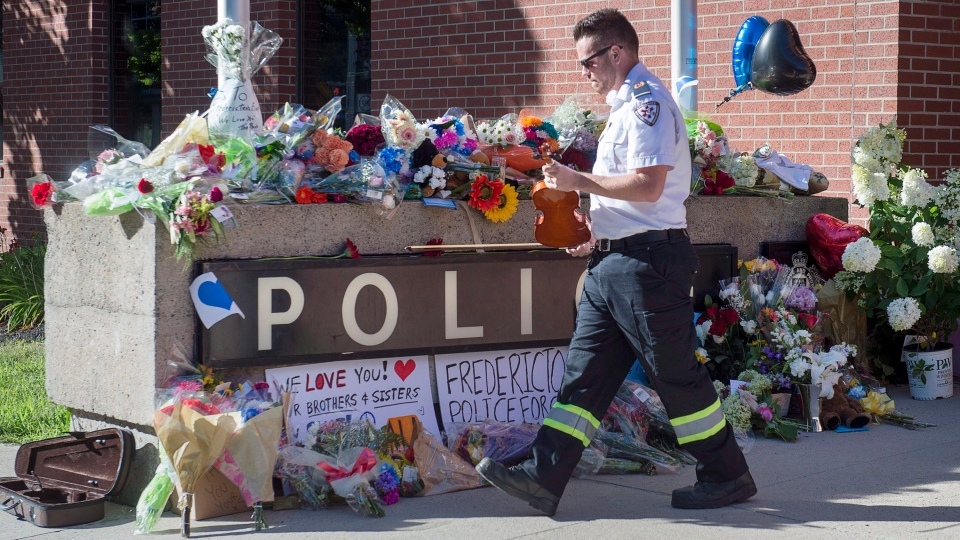 Paramedic Brian Fournier walks away after playing a hymn and placing a tribute at the police station in Fredericton on Friday, Aug. 10, 2018. Two city police officers were among four people who died in a shooting in a residential area on the city's north side. (THE CANADIAN PRESS / Andrew Vaughan)