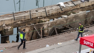 Two police officers work at the scene the day after an oceanside boardwalk collapsed during a nighttime concert in Vigo, Spain, Monday, Aug. 13, 2018. Authorities say the oceanside boardwalk collapsed around midnight Sunday at the closing event of a three-day festival, injuring 313 people, five of them seriously. (AP Photo/Lalo R. Villar)