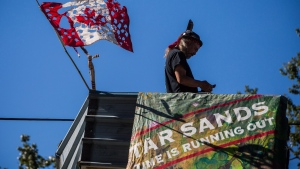 A man known as Blackwolf stands on top of a structure at Camp Cloud near the entrance of the Kinder Morgan Trans Mountain pipeline facility in Burnaby, B.C., on Saturday July 21, 2018.( THE CANADIAN PRESS/Ben Nelms)