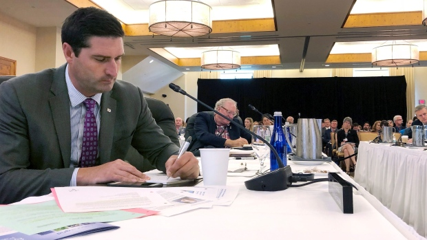 Geoff MacLellan, left, minister of trade for Nova Scotia, Prince Edward Island Premier Wade MacLauchlan, second from left, and Massachusetts Gov. Charlie Baker, far right, attend the Conference of New England Governors and Eastern Canadian Premiers on Monday, Aug. 13, 2018, in Stowe, Vt. (AP Photo/Lisa Rathke)