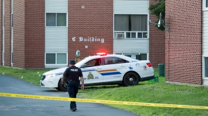 An RCMP officer walks the scene at an apartment building in Fredericton on Friday, August 10, 2018.  (THE CANADIAN PRESS/Andrew Vaughan)