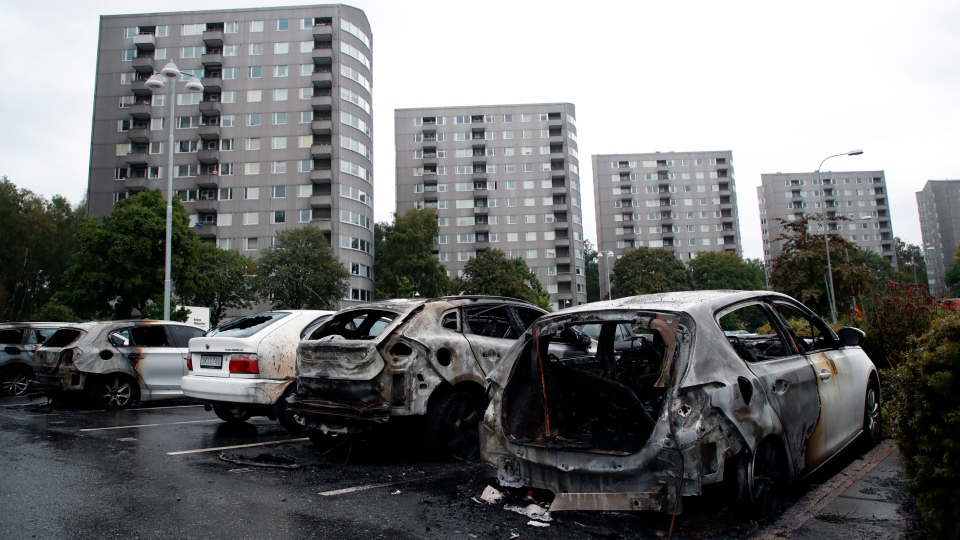 Burned cars parked at Frolunda Square in Gothenburg, Tuesday, Aug. 14, 2018. Masked youth torched dozens of cars overnight in Sweden and threw rocks at police, prompting an angry response from the prime minister, who on Tuesday spoke of an