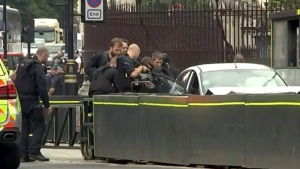 In this frame grab taken Tuesday, Aug. 14, 2018 armed police train their weapons on a car crashed into security barriers outside the Houses of Parliament stands to the right of a bus in London. London police say that a car has crashed into barriers outside the Houses of Parliament and that there are a number of injured. (ITN via AP)