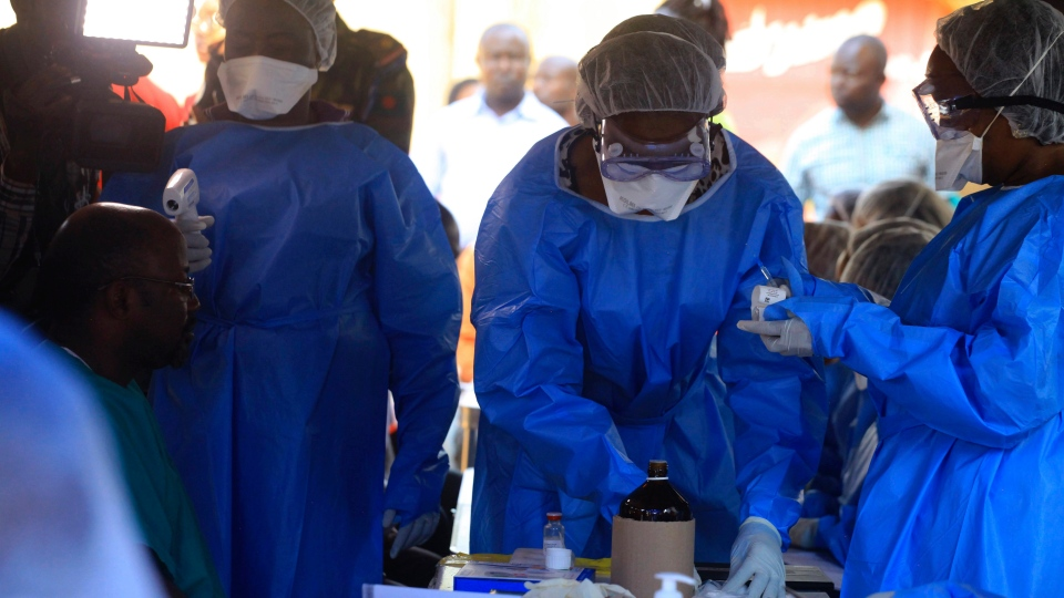 Healthcare workers from the World Health Organization prepare to give an Ebola vaccination to a front line aid worker in Beni Democratic Republic of Congo, Aug 10, 2018. (AP Photo/Al-hadji Kudra Maliro)