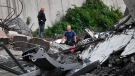 Rescues work among the debris of the collapsed Morandi highway bridge in Genoa, Tuesday, Aug. 14, 2018. (Luca Zennaro/ANSA via AP)