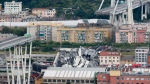 Cars are blocked on the Morandi highway bridge after a section of it collapsed, in Genoa, northern Italy, Tuesday, Aug. 14, 2018. (AP Photo/Antonio Calanni)