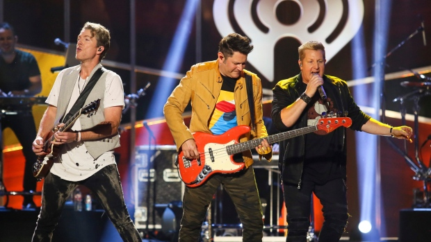 In this May 6, 2017, file photo, Rascal Flatts' Joe Don Rooney, Jay DeMarcus and Gary LeVox, from left, perform at the iHeartCountry Festival at the Frank Erwin Center in Austin, Texas. (Photo by Jack Plunkett]/Invision/AP, File)