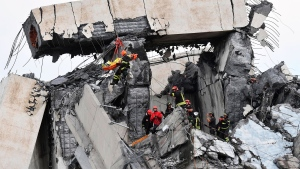 Firefighters rescue a person from the rubble of the collapsed Morandi highway bridge in Genoa, northern Italy, Tuesday, Aug. 14, 2018. A large section of the bridge collapsed over an industrial area in the Italian city of Genova during a sudden and violent storm, leaving vehicles crushed in rubble below. (Luca Zennaro/ANSA via AP)