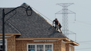 A construction worker shingles the roof of a new home in a development in Ottawa on Monday, July 6, 2015. (Sean Kilpatrick / THE CANADIAN PRESS)