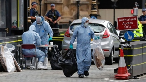 Forensics officers carry away bags from the car that crashed into security barriers outside the Houses of Parliament in London, Tuesday, Aug. 14, 2018. Authorities said in a statement Tuesday that a man in his 20s was arrested on suspicion of terrorist offenses after a silver Ford Fiesta collided with a number of cyclists and pedestrians before crashing into the barriers during the morning rush hour. (AP / Frank Augstein)