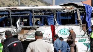 Rescue workers attend a Colombian-registered bus traveling to Quito, that crashed in Pifo, Ecuador, Tuesday, Aug. 14, 2018. (AP Photo/Carlos Noriega)