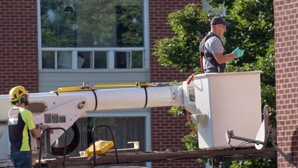 An RCMP forensic investigator prepares to examine a building adjacent to where Matthew Vincent Raymond is alleged to have gone on a shooting spree in Fredericton on Saturday, August 11, 2018. Two city police officers were among four people who died in a shooting in a residential area on the city's north side. (THE CANADIAN PRESS/Andrew Vaughan)