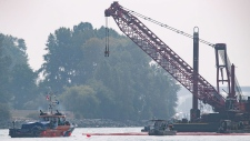 Spill response workers on boats and a crane on a barge are seen after a tugboat capsized and sank on the Fraser River between Vancouver and Richmond, B.C., on Aug. 14, 2018. (THE CANADIAN PRESS/Darryl Dyck)