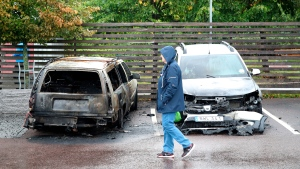 A person walks past burned cars parked at Frolunda Square in Gothenburg, Tuesday, Aug. 14, 2018. (Adam Ihse/TT via AP)