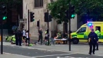 In this frame grab provided by UK Newsflare, emergency services attend the wounded after a car crashed into security barriers outside the Houses of Parliament in London, Tuesday, Aug. 14, 2018. (UK Newsflare via AP)