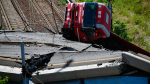 A truck lies on a side over the rubble of the collapsed Morandi highway bridge in Genoa, northern Italy, Wednesday, Aug. 15, 2018. (Luca Zennaro/ANSA via AP)