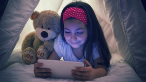 Encouraging kids to avoid using electronic devices in the dark is one way to limit the potential damage caused by too much screen time. (Gordana Jovanovic / Istock.com)