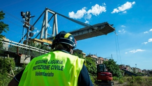 A worker inspects the the area around the collapsed Morandi highway bridge, in Genoa, northern Italy, Wednesday, Aug. 15, 2018. (AP Photo/Nicola Marfisi)