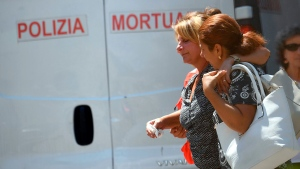 Relatives of victims walk outside the morgue of the San Martino hospital, in Genoa, Italy, Thursday, Aug. 16, 2018.  (Luca Zennaro/ANSA via AP)