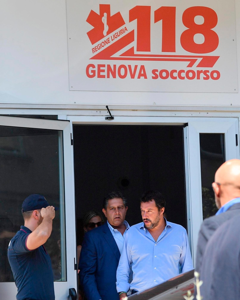 Italian Interior Minister Matteo Salvini, center right, is saluted as he is accompanied by Liguria Governor Giovanni Toti, after visiting injured victims of of highway bridge collapse, at the San Martino hospital, in Genoa, Italy, Thursday, Aug. 16, 2018  (Luca Zennaro/ANSA via AP)