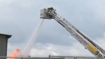 A Waterloo fire fighter operating a hose to tackle the fire from above.