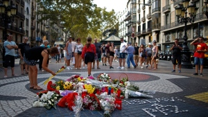A woman places a flower around a memorial tribute of flowers, messages and candles on Barcelona's historic Las Ramblas in Barcelona, Thursday, Aug. 16, 2018. (AP Photo/Manu Fernandez)