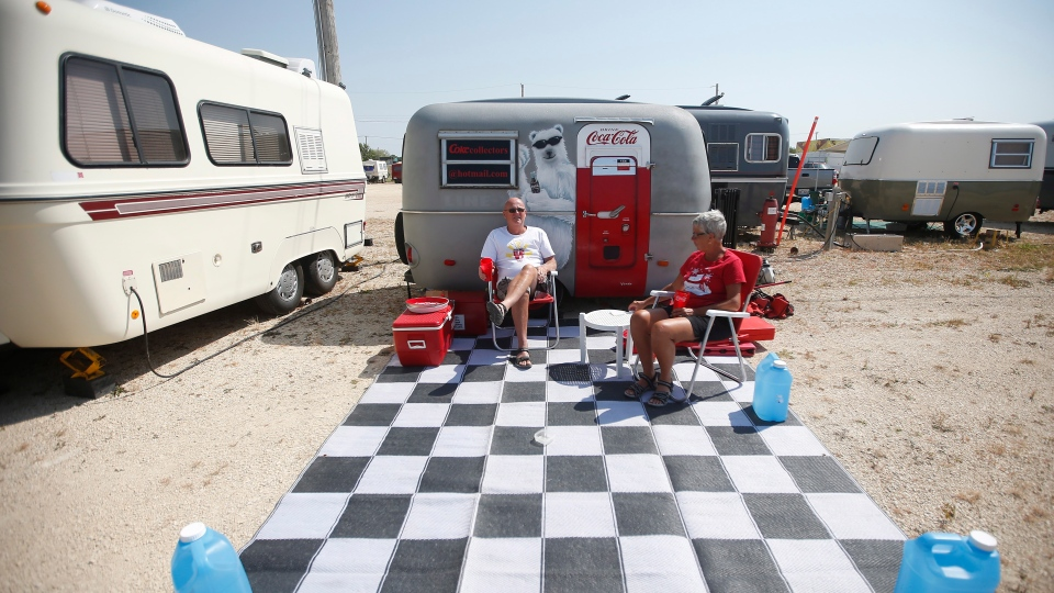Patsy and Richard Wiebe relax in front of their Coke themed trailer at the Boler 50th anniversary celebration weekend in Winnipeg on Wednesday, August 15, 2018. THE CANADIAN PRESS/John Woods