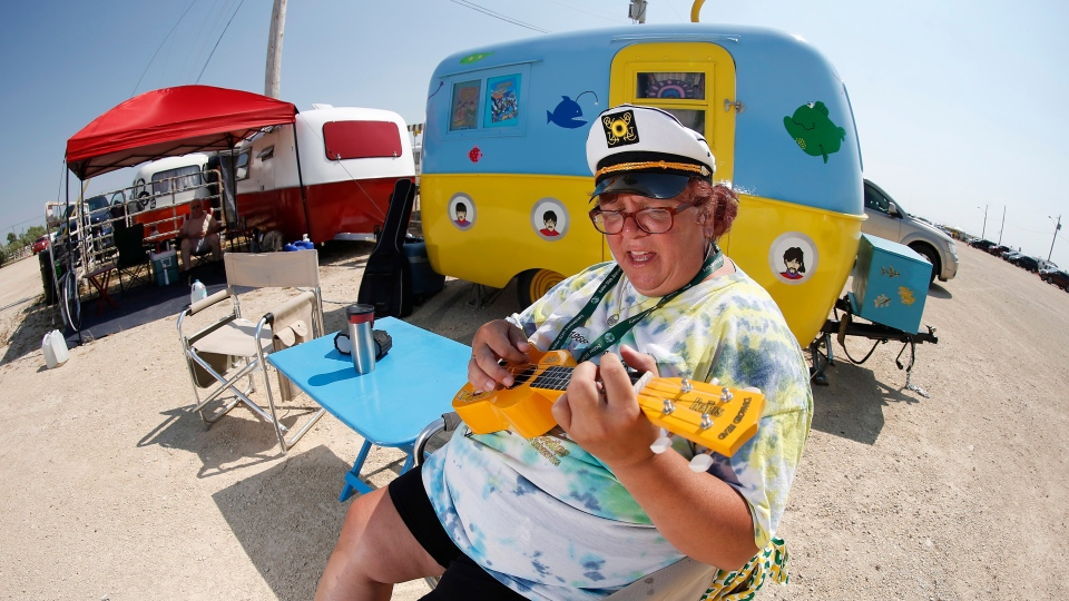 Angela Durand plays the ukulele outside her Yellow Submarine themed trailer at the Boler 50th anniversary celebration weekend in Winnipeg on Wednesday, August 15, 2018.  THE CANADIAN PRESS/John Woods