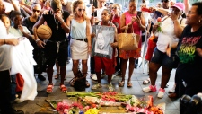 People gather at a makeshift memorial at the nameplate for singer Aretha Franklin outside the Apollo Theater Thursday, Aug. 16, 2018, in New York. Franklin died in her home in Detroit at age 76 from pancreatic cancer. (AP Photo/Frank Franklin II)