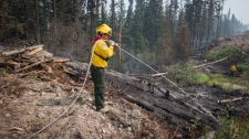 Firefighters Christian Garcia, left, and Felix Flores, back right, both from Mexico, deal with hotspots in an area burned by the Shovel Lake wildfire near Endako, B.C., on Thursday, August 16, 2018. THE CANADIAN PRESS/Darryl Dyck
