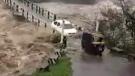 Vehicles hazard nearly-flooded bridge