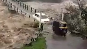 Vehicles hazard nearly-flooded bridge