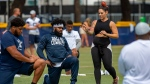 In this July 28, 2018, file photo, Dallas Cowboys offensive tackle La'el Collins, left and running back Ezekiel Elliott, center, listen to yoga instructor Stacey Hickman, right, as the team does some flexibility exercises at NFL football training camp in Oxnard, Calif. (AP Photo/Gus Ruelas, File)