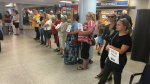 Volunteer drivers wait in the arrivals lounge of the Fredericton airport for incoming law enforcement personnel who are coming to the city to attend Saturday's regimental funeral for two police officers killed last Friday. (JONATHAN MACINNIS / CTV ATLANTIC)