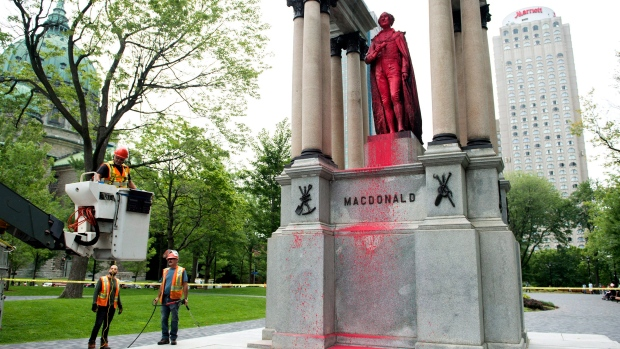City workers begin cleaning the statue of Sir John A. Macdonald after it was vandalized in Montreal, Friday, August 17, 2018.THE CANADIAN PRESS/Graham Hughes