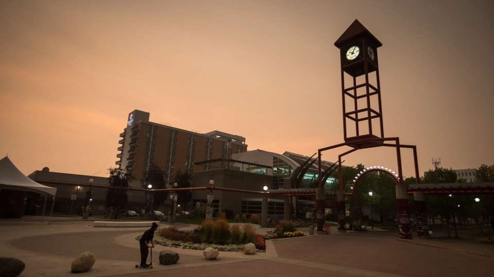 A woman rides a scooter just after 10 a.m. in near darkness due to thick smoke blanketing the city due to wildfires in the region, in Prince George, B.C., on Friday, Aug. 17, 2018. (Darryl Dyck / The Canadian Press)