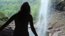 A woman is seen walking toward a waterfall in this undated image.