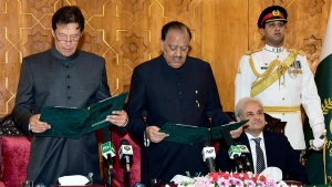 In this photo released by Pakistan's Press Information Department, Pakistani President Mamnoon Hussain, center, administers oath to newly-elected Prime Minister Imran Khan, left, at Presidential Palace in Islamabad, Pakistan, Saturday, Aug. 18, 2018.  (Press Information Department via AP)