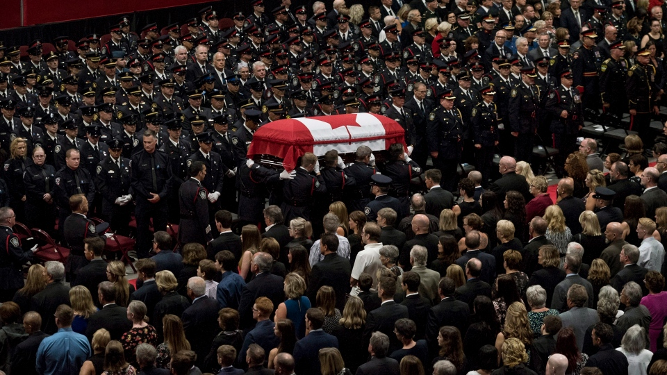 The flag-draped casket of slain Fredericton police officer Cst. Sara Burns is carried past members of the Fredericton Police department, family, and friends during a regimental funeral for Cst. Robb Costello and Cst. Burns on in Fredericton on Saturday, August 18, 2018. THE CANADIAN PRESS/Darren Calabrese