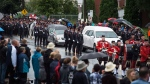 The hearses carrying two slain Fredericton Police officers Cst. Sara Burns and Cst. Robb Costello move slowly past residents of Fredericton during a regimental funeral on Saturday, August 18, 2018. THE CANADIAN PRESS/Darren Calabrese