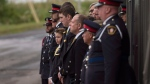 Family and friends of slain Fredericton Police officers Const. Sara Burns and Const. Robb Costello watch as hearses carrying their loved ones' caskets pull away following a regimental funeral in Fredericton on Saturday, August 18, 2018. THE CANADIAN PRESS/Darren Calabrese