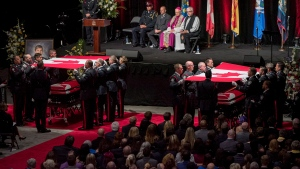 The Canadian flags are lifted off the caskets of slain Fredericton Police officers Const. Sara Burns and Const. Robb Costello during a regimental funeral in Fredericton on Saturday, August 18, 2018. THE CANADIAN PRESS/Darren Calabrese