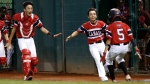 Canada's Nate Colina (5) is greeted by Andre Juco, left, and Jordan Jaramillo after scoring the winning run in the 10th inning against Spain in an elimination baseball game at the Little League World Series tournament in South Williamsport, Pa., Saturday, Aug. 18, 2018. (Tom E. Puskar / The Associated Press)