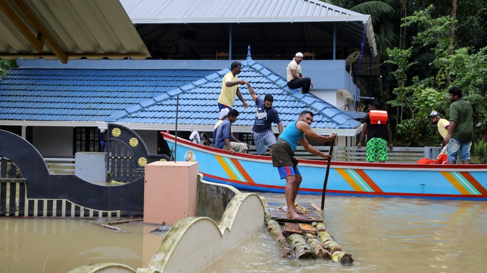 Volunteers rescue stranded people from a flooded area in Chengannur in the southern state of Kerala, India, Sunday, Aug.19, 2018. Some 800,000 people have been displaced and over 350 have died in the worst flooding in a century. (AP Photo/Aijaz Rahi)