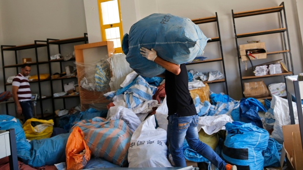 Palestinian postal workers sift through eight years' worth of undelivered mail held by Israel, at the post office in the West Bank city of Jericho, Sunday, Aug. 19, 2018. (Nasser Shiyoukhi / The Associated Press)