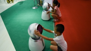 Children play with robots at the 2018 World Robot Conference in Beijing on August 15, 2018. (Wang Zhao / AFP)